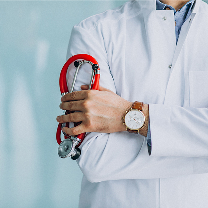 Doctor Standing wearing his Lap coat holding stethoscope & wearing analog watch in same hand with hand crossing posture Shows He is Satisfies With PRG Billing Services